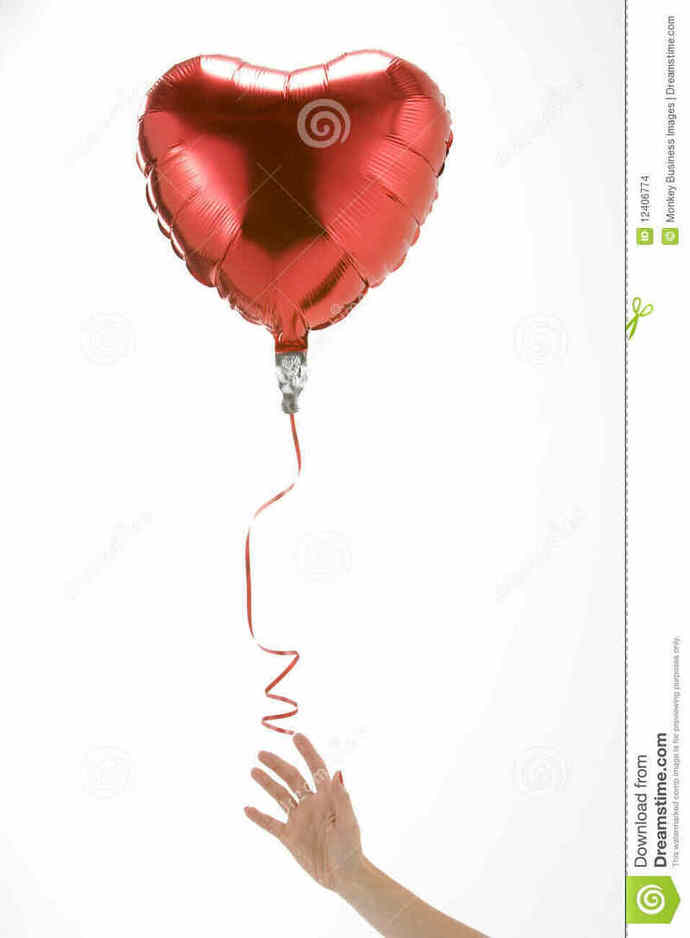 A hand letting go of a heart-shaped balloon