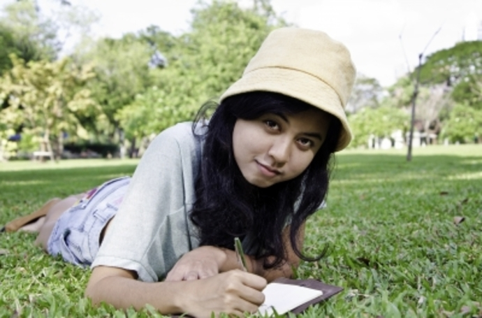 young woman on grass writing